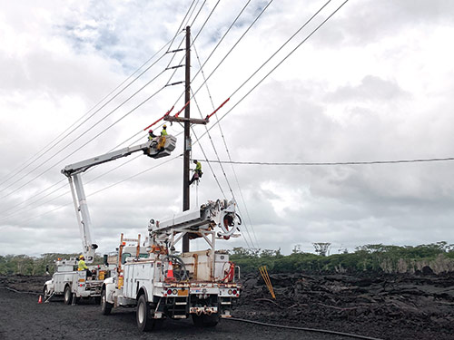 Hawaiian Electric is working closely with Ormat Technologies to bring the Puna Geothermal Venture plant back online. Here, utility linemen are restoring a line to bring some power in for the reconstruction project.